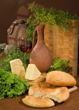 Bread, Wine And Greenery. Still life with bread and ceramic jar stock photo