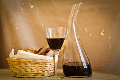 Bread and wine, landscape. A glass of wine with a decanter and a basket of home-made bread Stock Photo