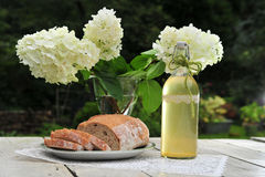 Bread and wine. Outdoor still life of home made bread, a bottle of wine or elder syrop and white hydrangea flowers on a garden table. Romantic athmosphere Royalty Free Stock Photography