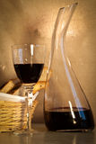 Bread and wine, portrait. A glass of wine with a decanter and a basket of home-made bread, portrait orientation Stock Image