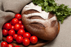 Bread on a wooden board with tomatoes Royalty Free Stock Image