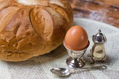 Bread on the wooden table and serviette, egg in silver utensil Royalty Free Stock Image