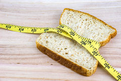 Bread wrapped with measuring tape on wooden surface Stock Images