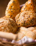 Breadbasket with whole wheat and chocolate buns and bread rolls. Close up of breadbasket with whole wheat and chocolate buns and bread rolls on brown warm Royalty Free Stock Photo