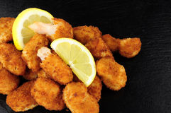 Breadcrumb Covered Fried Scampi On Slate Background. Crispy breadcrumb covered fried scampi on a slate background Stock Photos