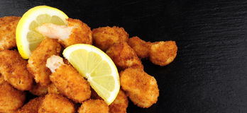 Breadcrumb Covered Fried Scampi On Slate Background. Crispy breadcrumb covered fried scampi on a slate background Royalty Free Stock Photo