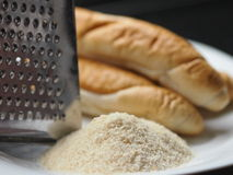 Breadcrumbs production. Pile of breadcrumbs, grater and white bread rolls - all you need for breadcrumbs production stock photos