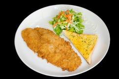 Breaded briet Fische mit dem Brot und Gemüse, die auf dem blac lokalisiert wurden Lizenzfreies Stockfoto