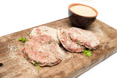 Breaded burgers. Breaded fresh beef burgers on cutting board Royalty Free Stock Images