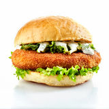 Breaded chicken burger with fresh salad. Side view of breaded chicken burger with fresh salad on white background stock photography