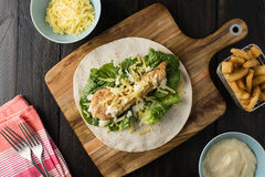 Breaded Chicken burrito Wrap With Fresh Lettuce Cheese. On rustic background Stock Photography