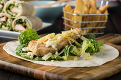 Breaded Chicken burrito Wrap With Fresh Lettuce Cheese. On rustic background Stock Photos