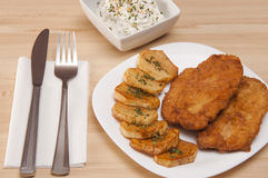 Breaded chicken fillet. With potatoes and cheese sesame salad Royalty Free Stock Images