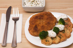 Breaded chicken portion. Breaded chicken fillet with potatoes, broccoli and cheese sesame salad Stock Photos