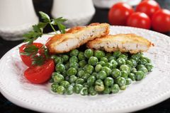 Breaded chicken steak with green peas Royalty Free Stock Photography