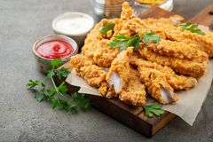 Breaded chicken strips with two kinds of sauces on a wooden Board. Fast food on dark brown background.  royalty free stock photos