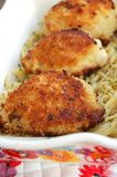 Breaded Chicken Thighs. Three breaded chicken thighs on top of garlic pasta in a dish royalty free stock photos