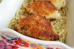 Breaded Chicken Thighs. Three breaded chicken thighs on top of garlic pasta in a dish stock photos