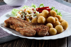 Breaded chop, prepared potatoes and salad Royalty Free Stock Images