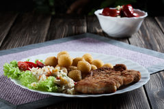 Breaded chop, prepared potatoes and salad Royalty Free Stock Photos