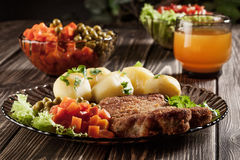 Breaded chop, prepared potatoes and salad Royalty Free Stock Image