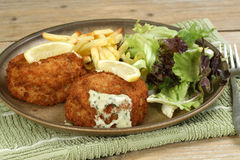 Breaded cod fish cakes. With parsley sauce salad and fries Stock Photography