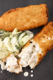 Breaded cod and fresh cucumber salad on slate Royalty Free Stock Image