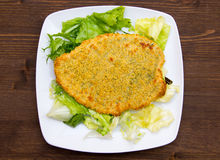 Breaded cutlet on wood from above Stock Image