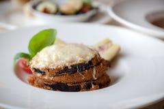 Breaded eggplant with tomato pesto, mozzarella and parmesan cheese with artichokes royalty free stock image