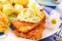Breaded fish for dinner. Breaded fish with potato and salad of sauerkraut for dinner Royalty Free Stock Photography