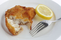 Breaded fish fillet with lemon and fork Royalty Free Stock Photography