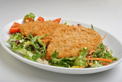 Breaded fish steak with herbs on a plate Royalty Free Stock Photography