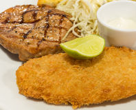 Breaded fish steak with a in selective focus. Breaded fish steak with steak or pork Royalty Free Stock Photos