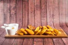 Breaded fried chicken nuggets and potatoes on cutting board and rustic wooden background Royalty Free Stock Photography