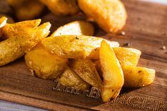 Breaded fried chicken nuggets and potatoes on cutting board and rustic wooden background Stock Photography