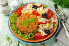 Breaded fried pork cutlet served with pasta salad Stock Photo
