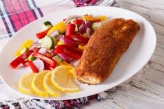 Breaded ha fritto il pesce con gli ortaggi freschi e un limone orizzontale fotografia stock