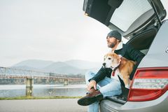 Breaded man in warm casual autumn outfit siting with beagle in c royalty free stock image