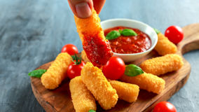 Breaded mozzarella cheese sticks in man hand with tomato basil sauce.  Royalty Free Stock Image