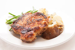 breaded pork chop with herb potatoes Stock Photo