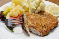 Breaded pork cutlet with boiled potatoes, cauliflower and hollandaise sauce Stock Photography