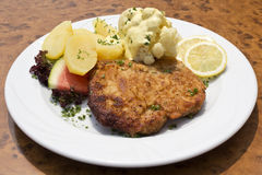 Breaded pork cutlet with boiled potatoes, cauliflower and hollandaise sauce Royalty Free Stock Photo