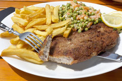 Breaded pork cutlet with peas and carrots, french fries Royalty Free Stock Image