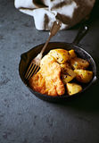 Breaded pork cutlet with potatoes on a frying pan Stock Image
