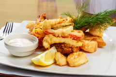 Breaded Prawns - King prawns coated in plain and spicy breadcrumbs and deep-fried. On white plate with full serving Royalty Free Stock Photos