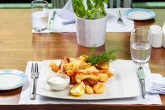 Breaded Prawns - King prawns coated in plain and spicy breadcrumbs and deep-fried. On white plate with full serving Stock Image