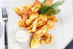 Breaded Prawns - King prawns coated in plain and spicy breadcrumbs and deep-fried. On white plate with full serving Royalty Free Stock Image