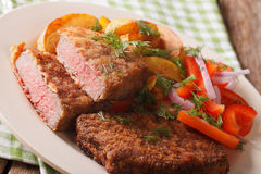 Breaded round steak with potato and vegetables close-up. horizon. Breaded round steak with potato and vegetables close-up on a plate. horizontal Royalty Free Stock Photo