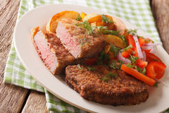 Breaded round steak and a side dish of vegetables close-up. hori. Breaded round steak and a side dish of vegetables close-up on a plate. horizontal Royalty Free Stock Photo