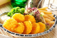 Breaded scallops. Fried breaded scallops with fries royalty free stock photo